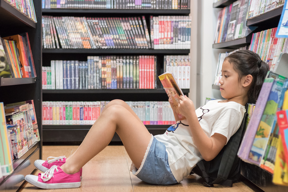 Girl Sitting on the Floor of a bookstore reading